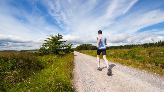 Mann rennt auf Feldweg